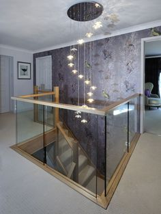 centrally-positioned oak and glass staircase with a half-landing turn and gallery landing.A centrally-positioned oak and glass staircase with a half-landing turn and gallery landing. Stair Landing Decor, Staircase Landing, Staircase Railings, Curved Staircase, Modern Staircase, Chandelier Staircase, Chandelier Lighting, Bannister, Stairways
