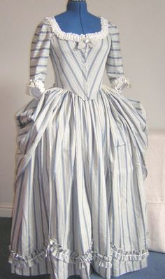 Polonaise Gown with front closure. Based on a pattern drawn from original garments by Janet Arnold, this gown dates from 1770-1780. The gown and skirt are fully lined, the top petticoat is unlined. The gown has sleeves to just below the elbow and optional sleeve frills, (engageants). The skirt is gathered with cartridge pleats and has two cords attached on the inside which are used to loop up the skirt.