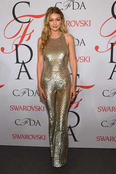 ELLE loves... Gigi Hadid wears a gold metallic catsuit with flared bottom at the CFDA Fashion Awards party in New York 2015.