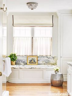 A silver-hued accent table adds a bit of sparkle to an elegant and classic bathroom in a Nashville house decorated by Markham Roberts. Waterworks' Boulevard fixtures complement the marble-top tub. Ceiling fixture, Chameleon Fine Lighting. House Beautiful
