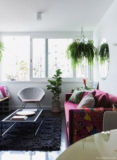 Sala de estar tem decoração nos tons preto, cinza e beringela. Pequenas árvores e plantas pendentes completam o decor.
