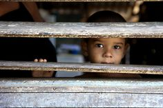 Cuban boy peeking through the blinds in Guantanamo, Cuba. #Cuba #Photography #Culture