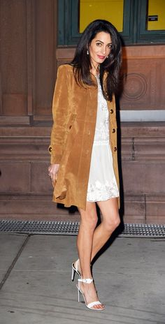 Amal Clooney wears a white lace-trimmed dress, suede coat, and white sandals