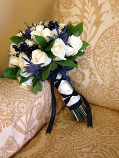 The bridal bouquet of cream roses, scottish thistle, tinted berries, greens and tied with tartan ribbon