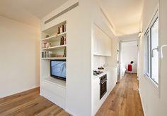 L'intervento è stato seguito dallo studio Sfaro Architects, il quale ha scelto di mettere a contrasto un arredo total white con il parquet color miele. Il miniappartamento si compone di bagno, zona gi