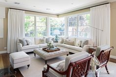 Gorgeous occasional chairs, custom upholstered ottoman, linen curtains, fabulous sofas, create a fabulous Hamptons style living room.  Journey Home Interior Design.