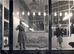 Etalage van Maison de Bonneterie aan de Kalverstraatzijde in Amsterdam. In de etalage een geschilderde impressie van het Damrak, gezien vanaf het Centraal Station naar de Dam.