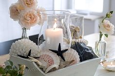 Nautical table decoration with beach finds, shells, sea stars and roses.