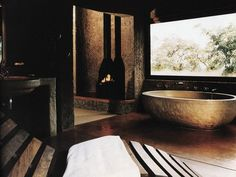 """Stone Palazzo Tubs are a favorite among South Africa's """"big five"""" game lodges because of their rugged finish that suits the surrounding landscape. To truly capture that out-of-Africa style, a safari game lodge used a rough stone appearance around the entire bathroom to create a dark, all-natural spa experience for guests. #diynetwork"""