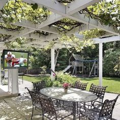 Exquisite Backyard Patio Dining Area With White Painted Wooden Pergola That Is Covered With Grape Vine