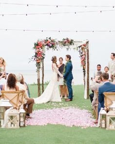 At model Renee Puente and actor Matthew Morrison's Hawaii destination wedding, the ceremony arch bloomed with roses, lisianthus, veronicas, passion vines, eucalyptus, and olive branches.