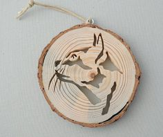 A rustic wood ornament depicting the profile of an inquisitive cat. (Some people think it looks like a bobcat).  A slice of wood from the limb of a pine tree is the base for this unique ornament. The cat was cut by hand, using a scroll saw. The bark is left on the wood, and the wood is unfinished for a very natural look.  The ornament is about 3 1/4 inches (8.3 cm) in diameter and 3/8 inch (11 mm) thick. It hangs from a silver screw eye, hanging from a hemp cord.  This one of a kind piece…