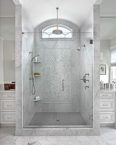 The large shower in the master bath features decorative marble tiles and three ways to shower. Marianne Jones LLC | Michigan Design Center