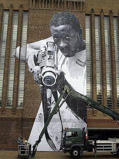 Street Artist JR proving a camera can be just as menacing as a gun...