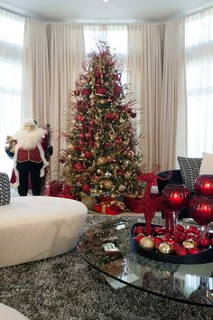A cheerful Santa guards the family room tree. Clusters of luminous ornaments in reds and golds vary in size.