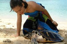 Girl of Tamil people and turtle on the beach in South India. Tamil people with a population of about 77 million living around the world are one of the largest and oldest of the existing ethno-linguistic cultural Nation in the Hindustan peninsula, India