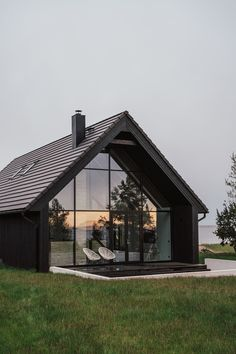 Two volumes with black exteriors form a summer house on Matsi Beach in Estonia, built on the remains of a Soviet-era fishing village by Hanna Karits. Houses In Poland, Modern Barn House, Modern Cabins, Black House Exterior, Small Beach Houses, Gable House, Prefab Cabins, Rural House, House Extensions