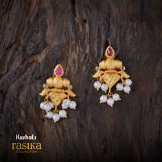 Triangular floral design rasika earrings studded with ruby stones at the top and tiny pearl drops plated with gold polish & made of pure 925 silver.