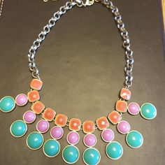 Bold Statement Necklace Dark silver colored bold statement necklace that will add a pop of color to any outfit! Thicker chained with orange, purple, and turquoise coloring in the main part of the necklace. Has a little bit of weight to it but sits wonderfully when you have it on! Jewelry Necklaces