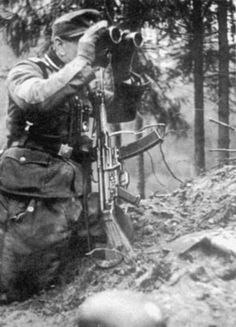 A German soldier of the 246th Volksgrenadier Division looks through binoculars during the Battle of the Bulge. He is equipped with the StG 44 assault rifle.