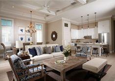 espacio moderno en colores claros con detalles en estampados, tapizado de sillón con motivos florales, cocina abierta en blanco y beige