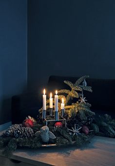 Beautiful Christmas decoration made with a candlestick, spruce branches, large cones and christmas ornaments.