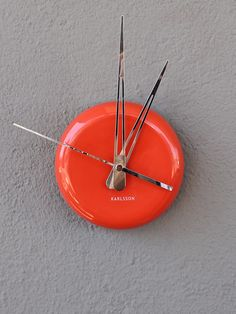 """simplistic in design  ceramic + metal come together as accent pieces on this round dot clock. striking in tangerine orange, it stands alone keeping time with style + ease. carry on the modern edge with this faceless design or sharpie your own numbers on for a one of a kind feel.  this clock keeps ticking on one AA battery  also available in slate grey + bright white  dimensions: 5""""dia.    sits 1 1/2"""" from wall"""