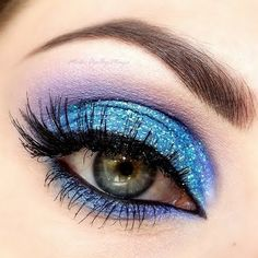 Bring disco fever back with this glittery blue and purple eye makeup. Wear it to a party.