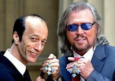 Robin, left, and Barry Gibb hold their Commanders of the Order of the British Empire decorations after receiving them from Prince Charles at Buckingham Palace on May 27, 2004. The third brother, Maurice Gibb, died the year before. His son Adam collected his decoration on his behalf.