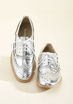 And now for your feature presentation - these metallic silver wingtips! Putting a flashy spin on the classic style, these thrilling, faux-leather kicks boast grey laces, terra-cotta colored soles, and tons of personality.