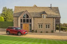 cotswold stone home with gravelled driveway and parked car