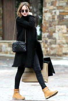 Dakota Johnson wearing Lito Large Tu Es Partout Rose Gold Diamond and Enamel Necklace, Chanel Black Quilted Lambskin Camera Bag with Tassel, Timberland Brookton 6-Inch Classic Boots in Wheat Nubuck, Isabel Marant Etoile Gresham Sweater, Joseph Anais Coat and Blk Dnm Black 26 Low-Rise Skinny Jeans