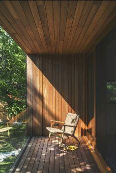 glass rail wood veranda overlooking a lush tropical garden accessed through wood framed glass doors maximising the natural light