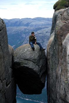 Tea in Norway...Kjeragbolten is a boulder wedged in a mountain crevice in the Kjerag mountains in Norway. Below the boulder is a sheer drop of about 3200 feet (1000 meters) to Lysefjorden.