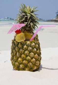 Tropical pineapple cocktail drink at the beach overlooking the ocean.