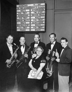 "Local 117 member, Abbie (Mrs. Roy) Keplinger, known professionally as ""Keppy,"" sits surrounded by the members of Keppy's Orchestra in the Crescent Ballroom at 13th & Fawcett. In July of 1955, the band was celebrating its 15th anniversary playing at the Ballroom. Fans from as far away as Seattle, Olympia and Portland would come to Tacoma to hear the Orchestra perform Dixieland, Hawaiian, modern hit tunes and dances of yesteryear."