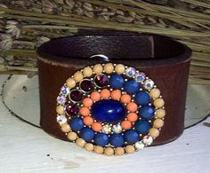 Classic beauty...Handmade from a multi-colored rhinestone pin and a gently aged, soft brown leather belt. Can be worn dressy or casual. Will fit wrist sizes 6.5-7.5 inches. Measures 1.5 inches wide.