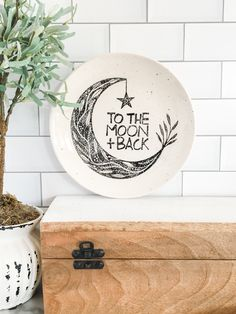 To The Moon & Back Trinket Plate There is something about a #lullaby that sparks inspiration. Something we took very seriously throughout this past year is the need to create more of what we love. Our new designs are the result of many laughs, not-so-quiet meditation, and the thought of listening to some #vintagevinyls. #handpainted #moonandback #baby #soinlove #nursery #treasure #giftsonline #museware #babygifts Birthday Plate, Baby Birthday Cakes, Ceramic Plates, Decorative Plates, Hand Drawn Lettering, Moon Design, Newborn Baby Gifts, Back Plate, Friendship Gifts