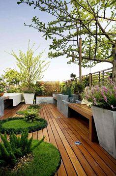 traumhafte- modern gestaltete Dachterrasse mit Holzdielen und großen Pflanzenkübeln aus Beton