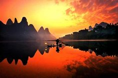 The shadowy mountain peaks contrast the gold tones of the sunset reflecting off of the Li River in China.  http://sussle.org/t/Sunset