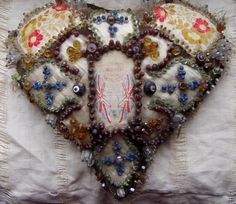 Sawdust-stuffed beaded heart: The ribbons were specially woven for soldiers and sailors for giving as gifts. Here the military ribbon forms the centre-piece of this ornate pinned and beaded heart.