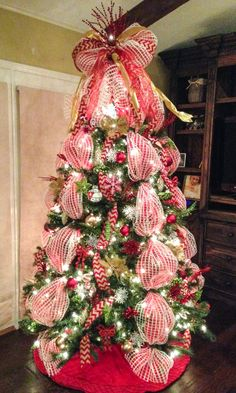 Deco mesh Christmas tree with red chevron burlap ribbon and mesh bow tree topper. Red deco mesh is layered under white window pane mesh for more depth and color.