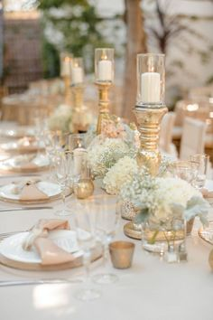 Glam gold decor, gold candle holders, baby's breath. Such a pretty table.