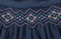 A beautiful new creation from Annette Grace Designs! This stunning and classy little navy blue dress is smocked across the front in lovely shades of blue and light rose. Little circles of pink bullion roses with green leaves and clusters of white pearls add sweet detail. The collars are round and white and finished with navy blue piping edging. The back is fastened together with three white buttons and a sash ties into a lovely bow. Edges are finished with a fine french seam and the generous…