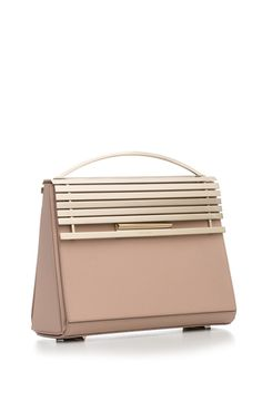 Eddie Borgo's premier handbag collection takes inspiration from the minimal yet futuristic automotive stylings of 1950s and 1960s chrome culture. This satchel by **Eddie Borgo** features an architectural body and a geometric aluminum foldover flap with top handle.