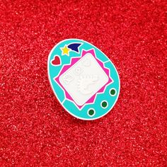 These cute Virtual Pet pins are made of hard enamel with a matte style finish and silver coloured inlay. They have a clutch back and measure 2.5cm x