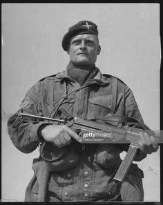 A British paratrooper holds a German submachine gun found in a cave. The weapon is believed to have been used to kill a British corporal. Pin by Poop stain