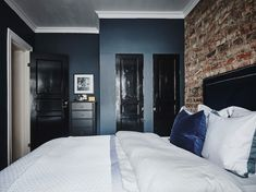 bedroom with brick wall, blue painted walls and black doors