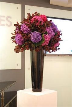 Large ball of purple and pink hydrangea on tall black vase at Mall Galleries