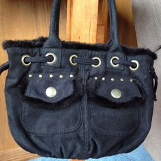 Black purse Suede like fabric purse with rivet and drawstring, faux fur around the top. 2 front small pockets, inside has a zip compartment. Small carrying handles. Brand unknown, gently used. Great to add to a bundle. Accessories